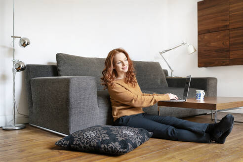 Full length of woman sitting with laptop while looking away in living room at home - DMOF00172