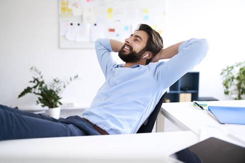Smiling businessman sitting at a desk - BSZF01133