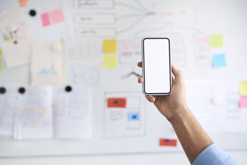 Male hand holding aloft a smartphone in front of a whiteboard - BSZF01139