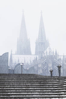 Low angle view of Cologne Cathedral and Museum Ludwig during snowfall in city against sky - GWF06137