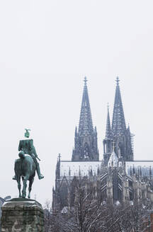 Low angle view of Kaiser Wilhelm II statue against Cologne Cathedral during winter in city - GWF06140