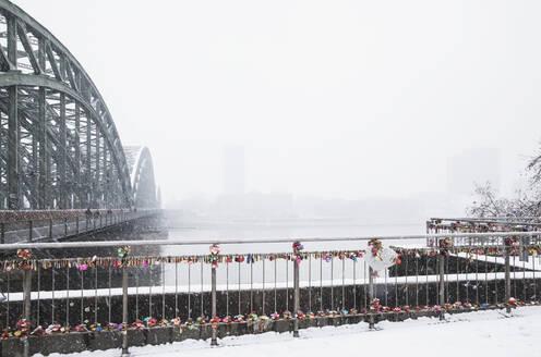 Padlocks on railing by Hohenzollern Bridge over Rhine river against sky during snowfall - GWF06146