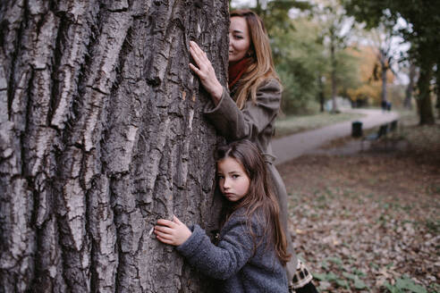 Portrait of little girl hugging tree with her mother - OGF00042