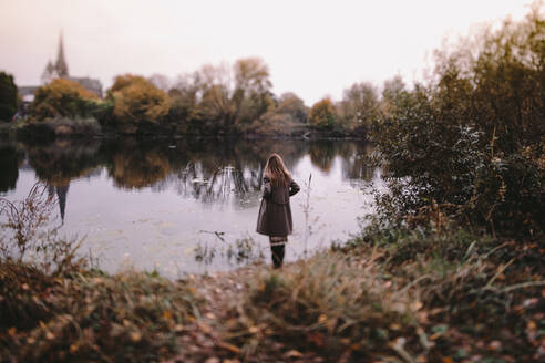 Back view of woman standing at water in autumn - OGF00048