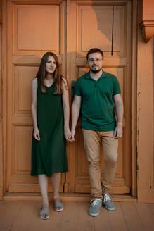 Portrait of couple standing hand in hand in front of wooden door at sunset - OGF00060