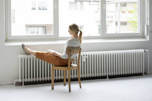Young woman sitting on chair at the window in office - JOSF03460