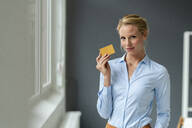 Portrait of young woman holding credit card - JOSF03484