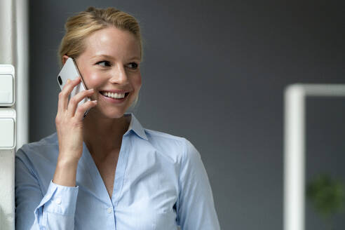 Smiling young businesswoman talking on cell phone in office - JOSF03487