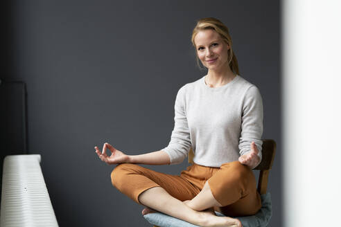 Young woman sitting on chair in office practicing yoga - JOSF03508