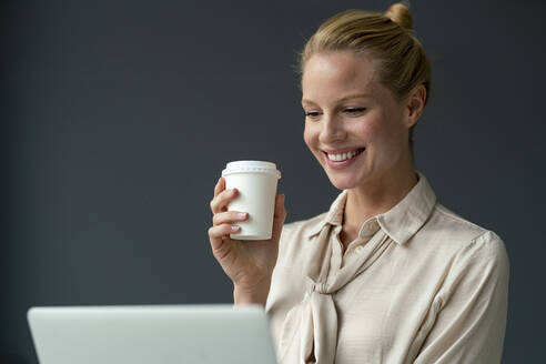 Smiling young businesswoman with laptop and takeaway coffee - JOSF03523