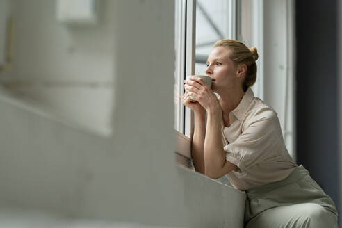 Young businesswoman with cup of coffee looking out of window - JOSF03532