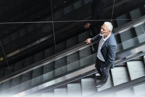 Mature businessman on an escalator - DIGF07405