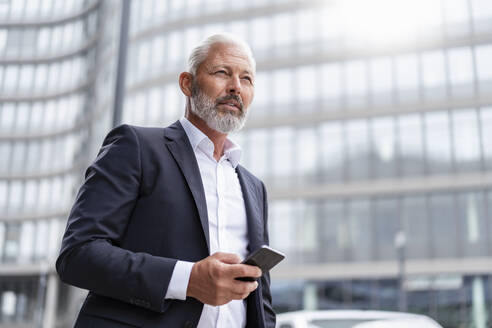 Mature businessman with cell phone in the city - DIGF07420