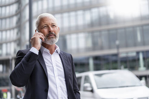 Mature businessman on cell phone in the city - DIGF07423