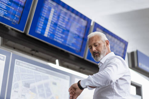 Mature businessman checking the time at departures board - DIGF07438
