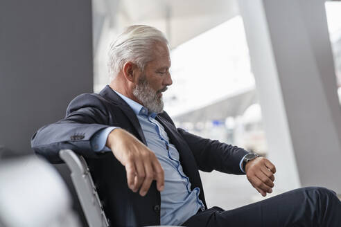 Mature businessman sitting in waiting area checking the time - DIGF07462
