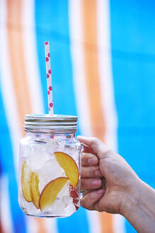 Close-up of Woman's hand holding drink in mason jar filled with ice and slices of peach - BZF00503