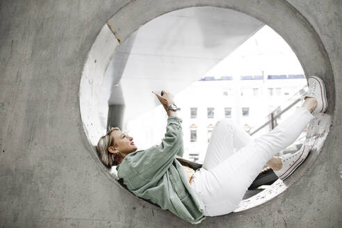 Full length of side view of mature woman using mobile phone while lying on concrete circle in wall - KMKF01005
