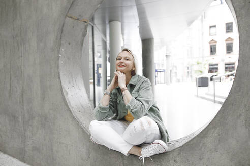 Full length portrait of beautiful mature woman smiling while sitting on concrete circle in wall - KMKF01008