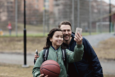 Smiling son taking selfie with father after basketball practice in winter - MASF12913