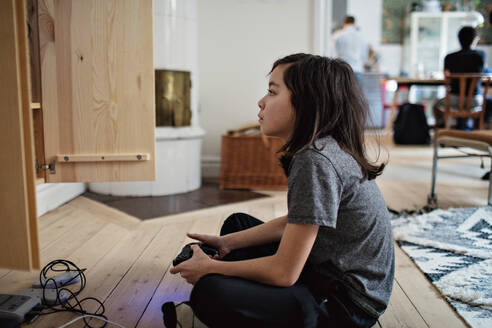 Side view of boy looking away while playing video game on hardwood floor at home - MASF12937