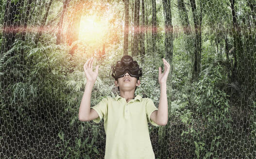 Mixed race boy wearing virtual reality goggles in remote forest - BLEF09705