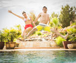 Couple jumping into swimming pool - BLEF09720