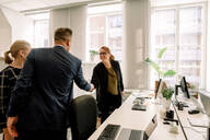 Businesswoman shaking hand with businessman while standing in office - MASF13057