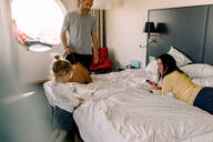 Man talking to happy woman looking at daughter standing by bed - MASF13063