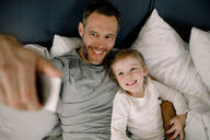 High angle view of happy father taking selfie with smiling daughter on bed in hotel - MASF13069