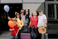 Portrait of cheerful family with luggage standing at hotel entrance during vacation - MASF13093