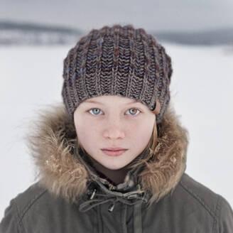 Caucasian teenage girl wearing beanie hat in snow - BLEF09753
