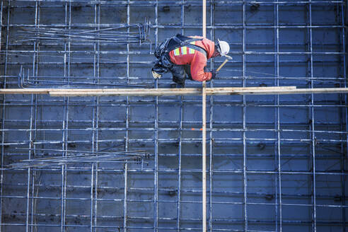 Caucasian worker nailing boards at construction site - BLEF09819
