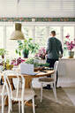 Full length rear view of man gardening in room at home - MASF13192