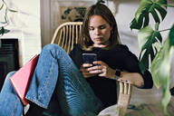 Woman sitting with book using smart phone on armchair in room at home - MASF13210