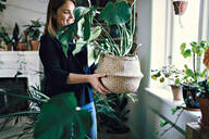 Smiling woman carrying wicker potted plant by window in room at home - MASF13219