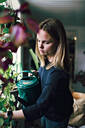 Female watering potted plants on window sill at home - MASF13237