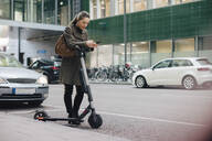 Full length of female commuter using smart phone on roadside in city - MASF13261