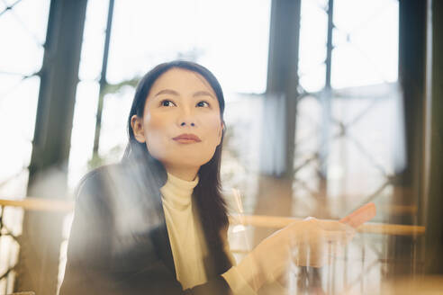 Confident businesswoman holding smart phone while looking away in office cafeteria - MASF13267