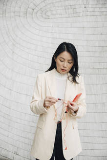 Confident businesswoman holding smart phone and earphones against wall at office - MASF13279