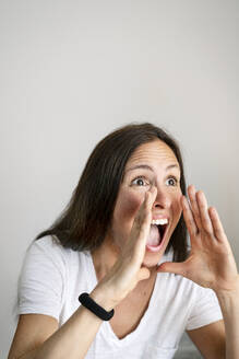 Mature woman shouting against white background - DMOF00186
