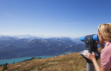 Woman looking at mountains through coin-operated binoculars from Schafberg against blue sky - GWF06157