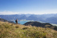 Mature woman hiking on grass at Schafberg Railway with Lake Wolfgangsee and Dachstein Mountains against blue sky - GWF06169