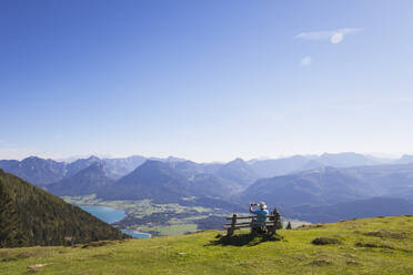 Rear view of senior male hiker photographing while sitting on bench while looking at Dachstein Mountains against blue sky - GWF06175