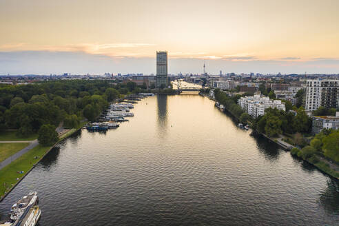 Spree river flowing amidst residential building seen from Treptower Park against sky during sunset - TAMF01830