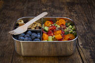 High angle view of fresh meal in lunch box with fork on wooden table - LVF08172