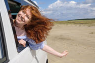 Portrait of carefree redhead teenage girl with head out of car window enjoying at beach against sky - LBF02625