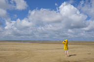Full length rear view of teenage girl wearing yellow raincoat while walking on sand at beach during sunny day - LBF02634