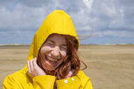 Close-up of carefree redhead teenage girl wearing yellow raincoat while standing at beach against sky on sunny day - LBF02637