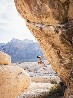 Mixed race girl rock climbing and falling from cliff - BLEF09952